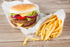 Big hamburger with french fries. Big fresh  hamburger with french fries on wooden table Royalty Free Stock Images