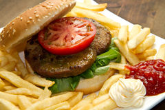 Big hamburger, French fries and vegetables Royalty Free Stock Images
