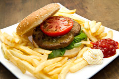 Big hamburger, French fries and vegetables Stock Photos