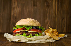 Big hamburger and french fries on a wooden background Royalty Free Stock Photography