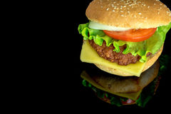 Big hamburger with fresh vegetables with reflection isolated on black Stock Photos