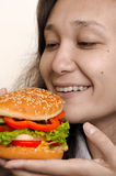 Big hamburger in girl hands meal time. Young woman eating junk food colorful appetizing hamburger royalty free stock photos