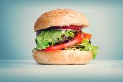 Big hamburger lays on the table Royalty Free Stock Image