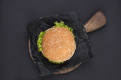 Big hamburger with sesame seeds on a black background. Fast food and free space for text. View from above. stock images