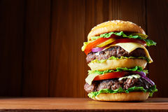 Big hamburger. On wooden background Stock Photos