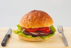 Big hamburger on the wooden plate Stock Photos