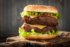 Big hamburger. On wooden rustic cutting board stock images