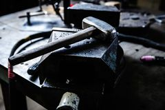 Big hammer on anvil in blacksmith workshop. Hammer on anvil  in smithery workshop.Professional blacksmith work table with incus for stamping metal products Royalty Free Stock Photo