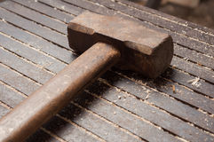 Big hammer on iron table with wooden dust Royalty Free Stock Images