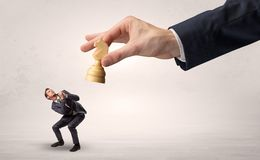 Big hand with chessman down small weak businessman concept. Big hand holding chessman and down little afraid businessman concept in a light spacen Stock Photo