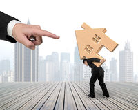 Big hand forefinger pointing at man carrying wooden house. On his back, with city skyscraper background Royalty Free Stock Photo