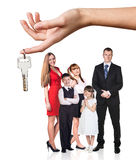Big hand give keys to young family Royalty Free Stock Photos