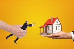 Big hand on the left holding small businessman reaching out with his both hands for small house standing on palm of the. Other hand on the right. Real estate royalty free stock photo