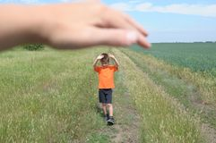 Big hand shelter little tiny boy in field. Big hand shelter little tiny boy in the field Stock Image