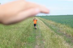Big hand shelter little tiny boy in field. Big hand shelter little tiny boy in the field Royalty Free Stock Photos