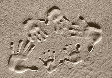 Big Hands, Little Hands. A family of handprints pressed into the sand Stock Photos
