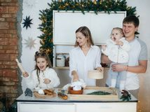 Big happy family baking with little daughters. On a kitchen Stock Photos