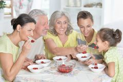 Portrait of big happy family eating fresh strawberries at kitchen stock photography