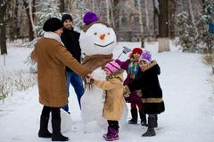 Big happy family: father, daughters and grandmother sculpt a big real snowman royalty free stock image