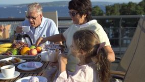 A big happy family has dinner on the open terrace on the roof of the house. stock footage