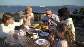 A big happy family has dinner on the open terrace on the roof of the house. Tea party on the summer terrace on the sea coast stock footage
