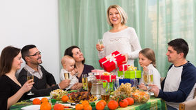 Big happy family home celebration. Happy relatives proposing a toast for family member with gifts at home celebration Royalty Free Stock Photos
