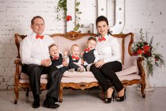 Big happy family: mother, father, triplet sons. Big happy family: mother, father and triplets sons in the studio Royalty Free Stock Photo