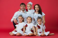 Big happy family: parents are father, mother and children are twins in embroidered dresses with an ornament on a red background in royalty free stock photos