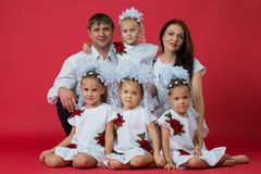 Big happy family: parents are father, mother and children are twins in embroidered dresses with an ornament on a red background in stock image