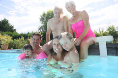 Big happy family by swimming pool enjoying. Happy 3-generation family enjoying swimming-pool Royalty Free Stock Photos