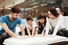 Big happy family testing orthopedic mattress in shop of furniture. Check softness of mattress. royalty free stock image