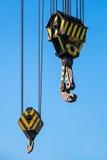 Big harbor cranes hooks hanging on ropes Stock Photography