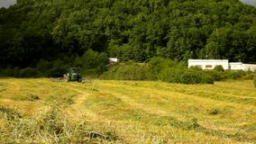 Big harvesting machine is turning above dry grass, truck with hay maker working on the meadow in farmland. stock video footage