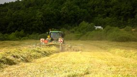 Big harvesting machine is turning above dry grass, truck with hay maker working on the meadow in farmland. stock video