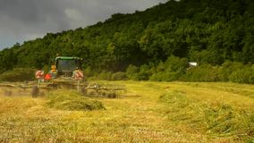 Big harvesting machine is turning above dry grass, truck with hay maker working on the meadow in farmland. Stock Images