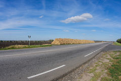 Big hay stack and a road daytime landscape. Big hay stack and a road daytime, rural landscape Royalty Free Stock Image