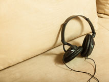 Big headphones lying on white sofa Royalty Free Stock Photos