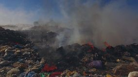 Big Heap Of Garbage Burning At Landfill. AERIAL VIEW. Camera moving above big garbage heap burning at suburbs producing smoke blown by the wind against blue sky stock footage