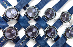 It is a lot of man's watch with the blue dial and blue a thong lies on a white background Stock Image