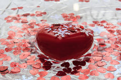 Big heart floats in water. Valentine`s day. A red heart. White snowflakes. A dish of water. Heart floats in water Royalty Free Stock Photo