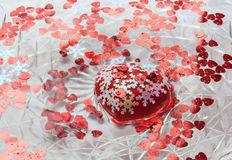 Big heart and little hearts floating in the water. Valentine`s d. A red heart. White snowflakes. A dish of water. Heart floats in water Stock Images