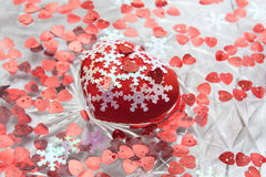 Big heart and little hearts in the water.  Valentine`s day. A red heart. White snowflakes. A dish of water. Heart floats in water Stock Photo