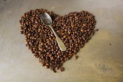 Big heart made of coffee beans and spoon Stock Photo
