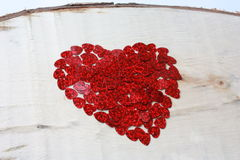 A big heart made of little hearts on a wooden board. A big heart made of little hearts. Red heart shiny hearts. A wooden plaque Stock Photo