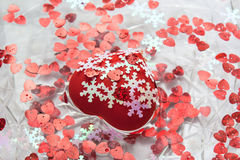 A big heart and many little hearts in water. A red heart. White snowflakes. A dish of water. Heart floats in water. Valentine`s day Royalty Free Stock Image