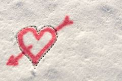 Big heart pierced by an arrow of love drawn in the snow in the winter Royalty Free Stock Photo