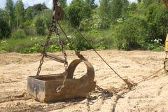 Big heavy bucket lies on sand on summer day Stock Image