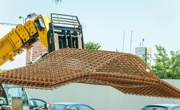 Big heavy construction machinery forklift transporting metal or steel reinforcement grid armature framework to building work site.  stock photography