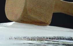 Big and heavy wooden hammer smashed ice brick on black background stock photos