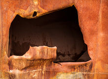 Big hole in rusty steel plate Royalty Free Stock Photos